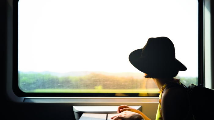 A beautiful hipster asian woman travelling on the train. Sitting on the black leather cozy comfort seat in the business class boky of the train in Europe. Tourist travel concept.; Shutterstock ID 1111543499; Purchase Order: -